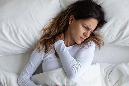 Femme au lit mal de cou