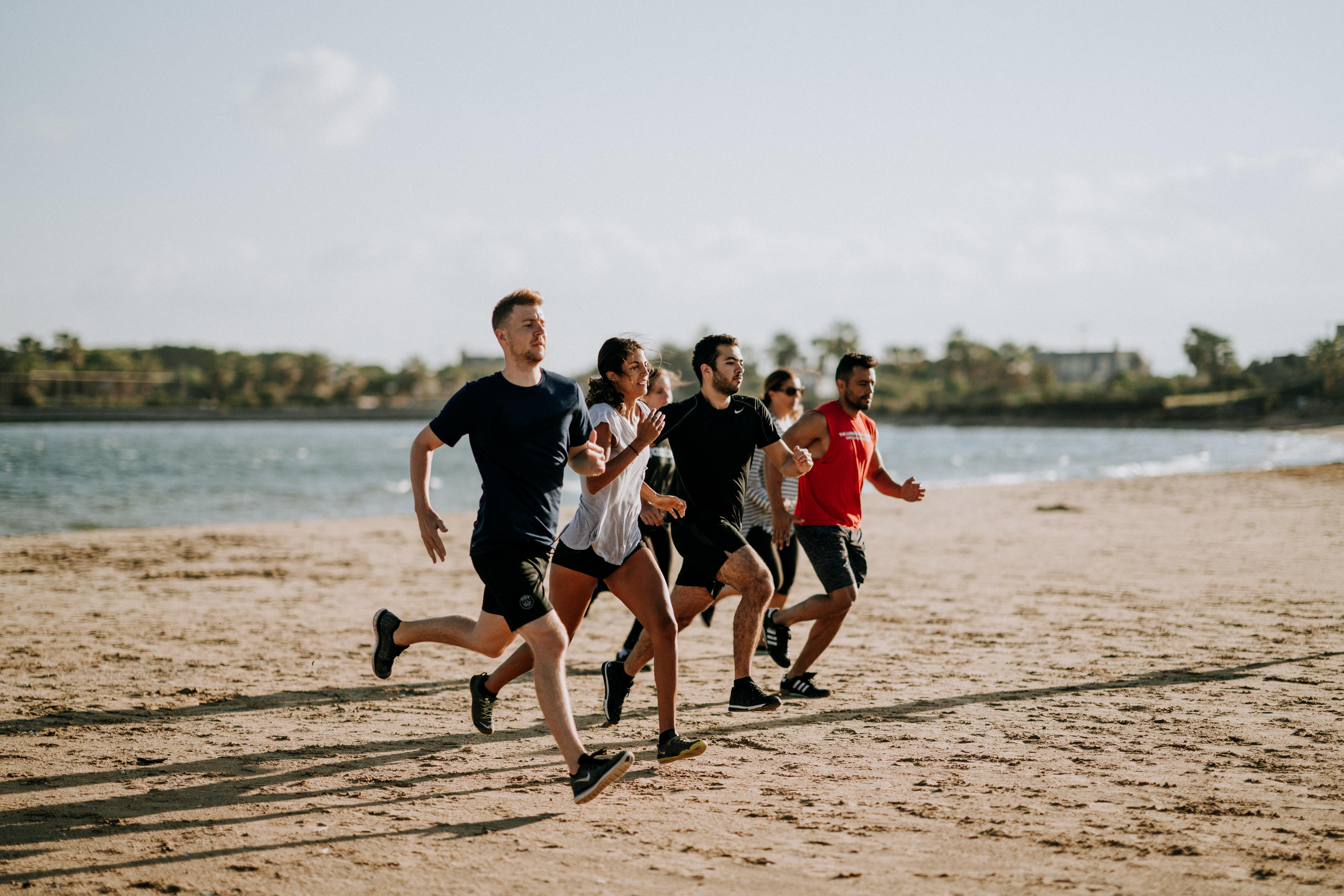 5 personnes qui courent sur une plage