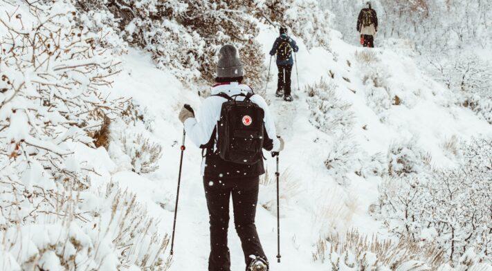3 personnes en raquette sur un sentier enneigé