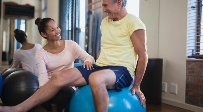 Thérapeute et un patient assis sur un ballon